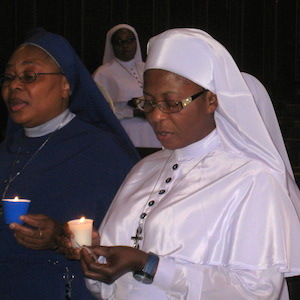 Nun praying with candle